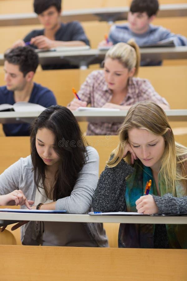Étudiants apprenant dans une salle de conférences avec une fille à l'aide du PC de comprimé images libres de droits