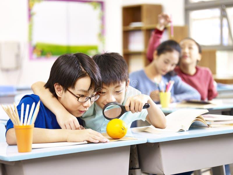 Étudiants asiatiques espiègles et curieux d'école primaire photographie stock