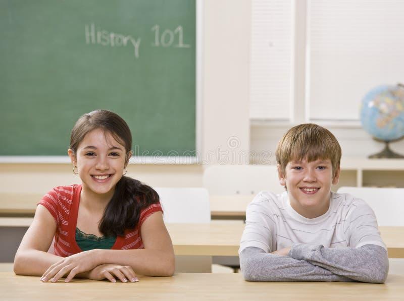 Étudiants au bureau dans la salle de classe images libres de droits