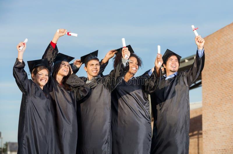 Étudiants avec des diplômes se tenant ensemble dessus images stock
