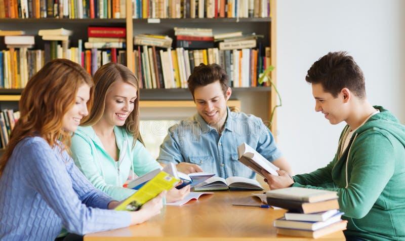 Étudiants avec des livres préparant à l'examen dans la bibliothèque photographie stock libre de droits