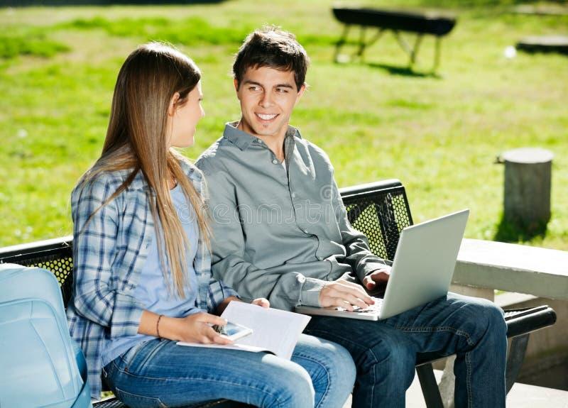 Étudiants avec le livre et l'ordinateur portable dans le campus images stock
