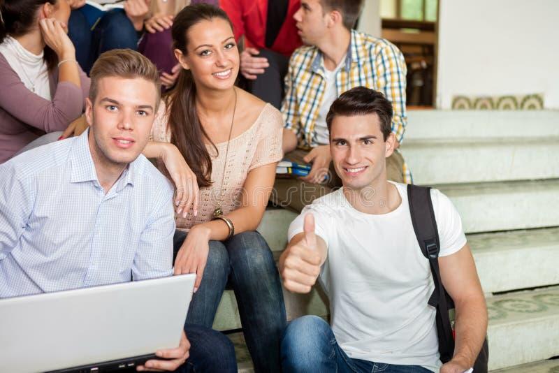 Étudiants ayant l'amusement avec des escaliers d'école d'ordinateur portable photos libres de droits