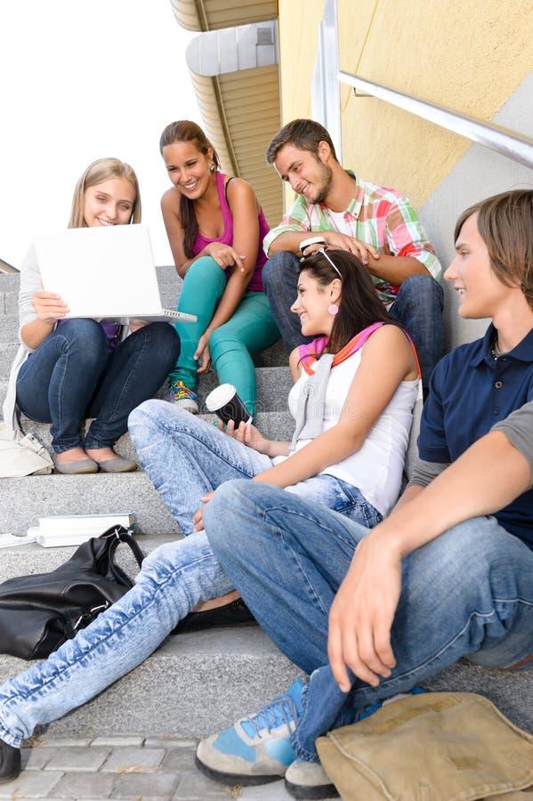Étudiants ayant l'amusement avec des escaliers d'école d'ordinateur portatif photographie stock