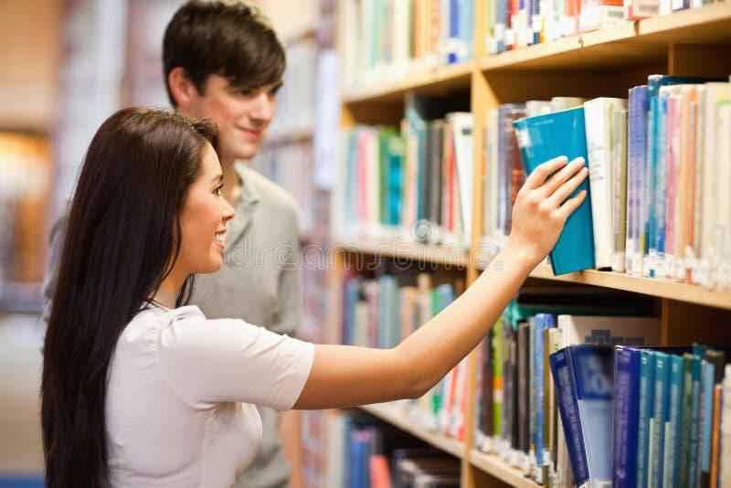 Étudiants choisissant un livre sur une étagère images stock