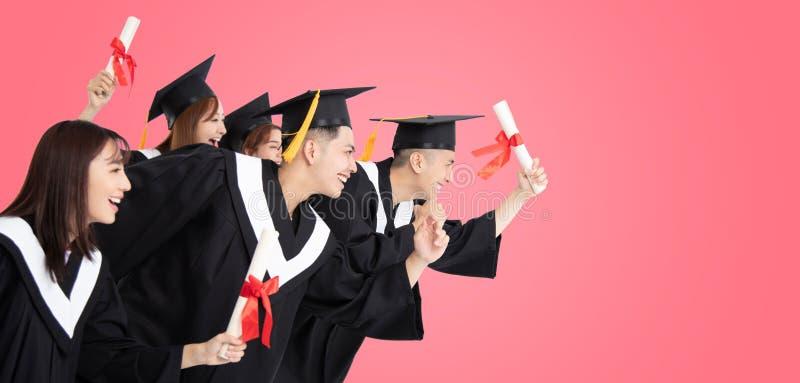 Étudiants courant et célébrant l'obtention du diplôme photos stock