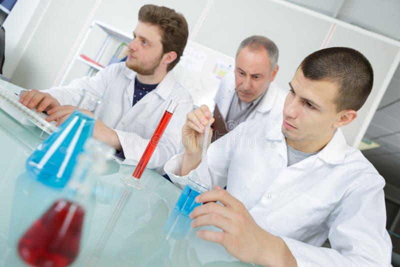 Étudiants d'école avec le professeur dans la classe de chimie photos libres de droits