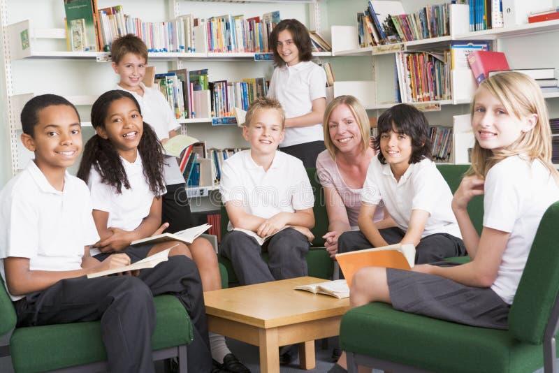 Étudiants d'école junior travaillant dans une bibliothèque photos libres de droits