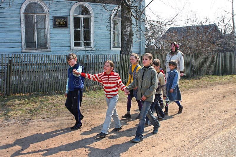 Étudiants d'école primaire rurale, marchant dans la rue de village, Rus image stock