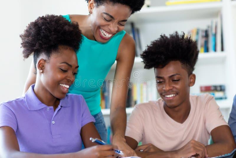 Étudiants d'afro-américain apprenant avec le professeur féminin mûr photos libres de droits