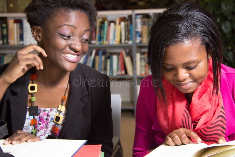 Étudiants d'afro-américain espiègles dans la bibliothèque image libre de droits