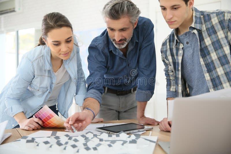 Étudiants d'architecture avec l'entraîneur travaillant sur le projet image libre de droits