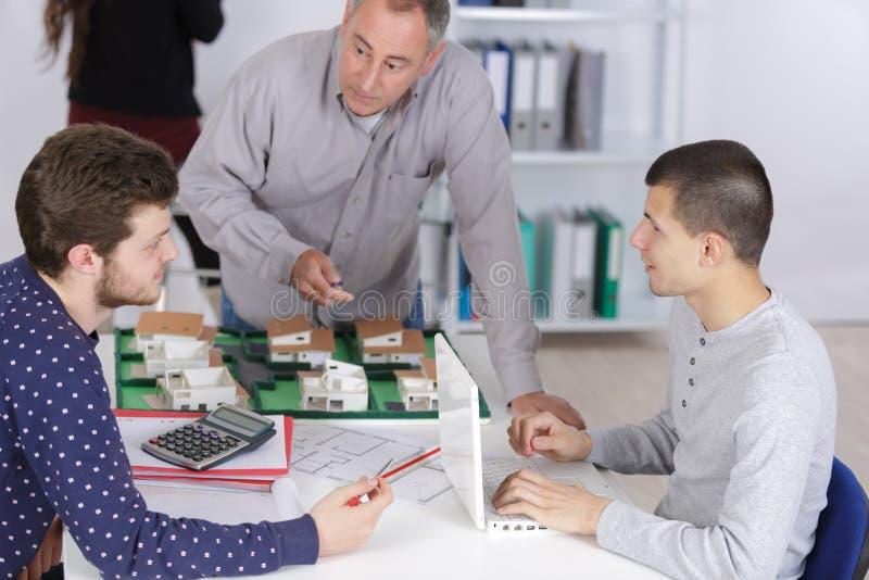 Étudiants d'architecture travaillant sur le modèle architectural dans l'atelier d'université photographie stock libre de droits