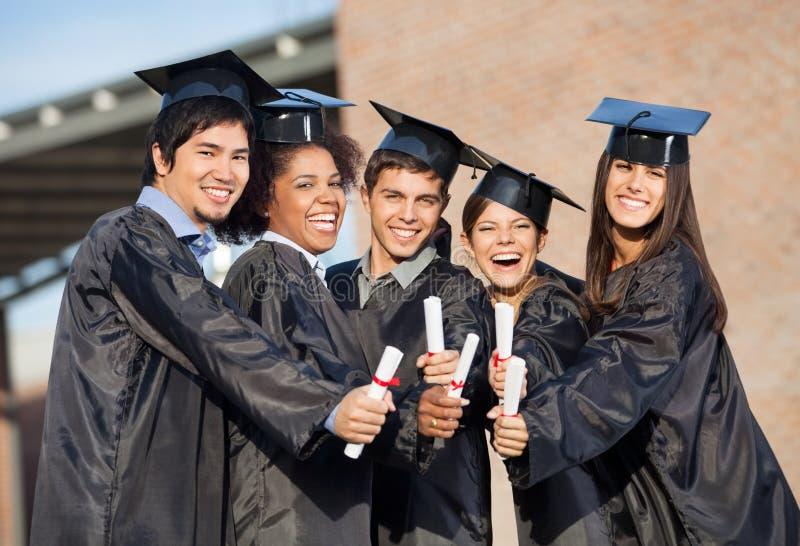 Étudiants dans des robes d'obtention du diplôme montrant des diplômes dessus photos stock