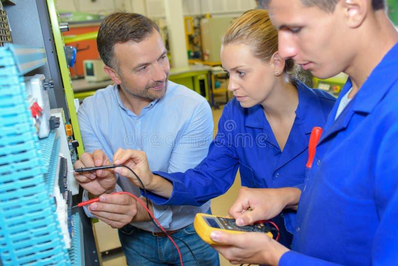 Étudiants de évaluation de professeur travaillant aux circuits électriques photographie stock libre de droits