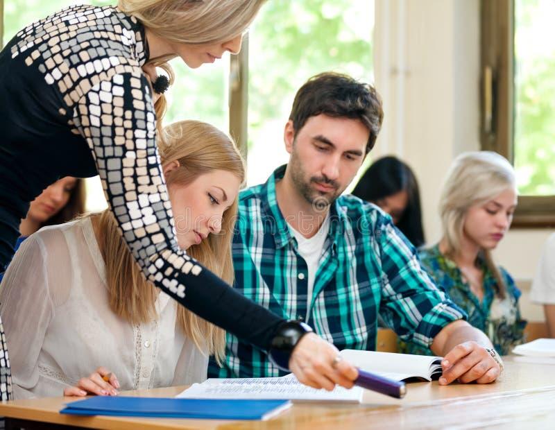 Étudiants de aide de professeur images stock