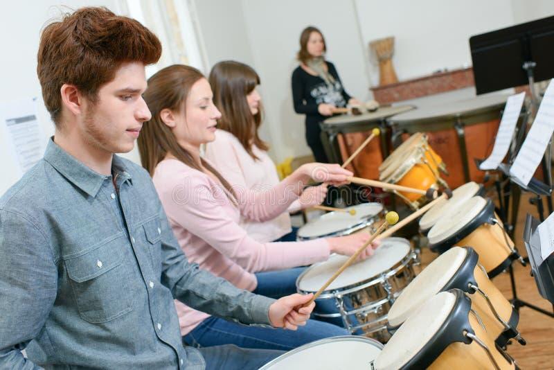 Étudiants de groupe jouant dans l'orchestre d'école ensemble image stock