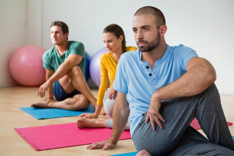 Étudiants de guidage d'instructeur de yoga en pratiquant Ardha Matsyendrasana photo stock