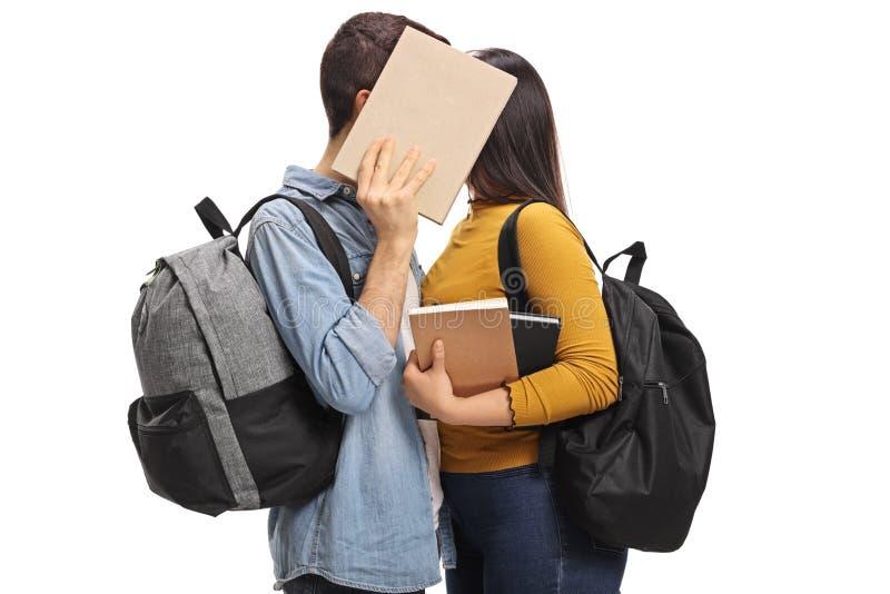 Étudiants de l'adolescence embrassant derrière un livre photo libre de droits