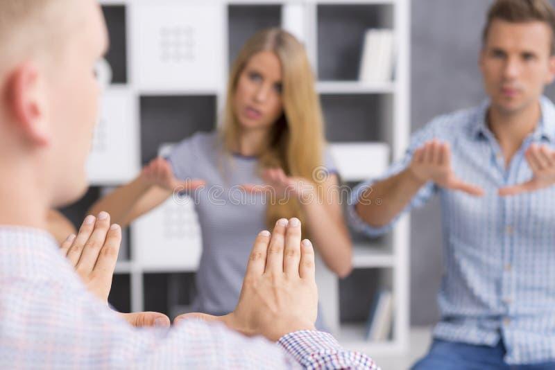 Étudiants de langue des signes répétant le nouveau signe après leur professeur images libres de droits