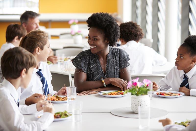 Étudiants de lycée de With Group Of de professeur féminin portant la séance uniforme autour du Tableau et mangeant le déjeuner da images stock