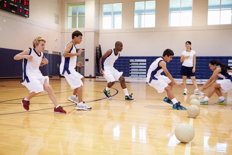 Étudiants de lycée jouant la boule de Dodge dans le gymnase photographie stock libre de droits