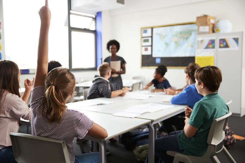 Étudiants de lycée soulevant des mains pour répondre à la question réglée par le professeur In Classroom images libres de droits