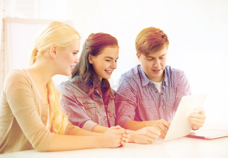 Étudiants de sourire avec l'ordinateur de PC de comprimé à l'école image libre de droits