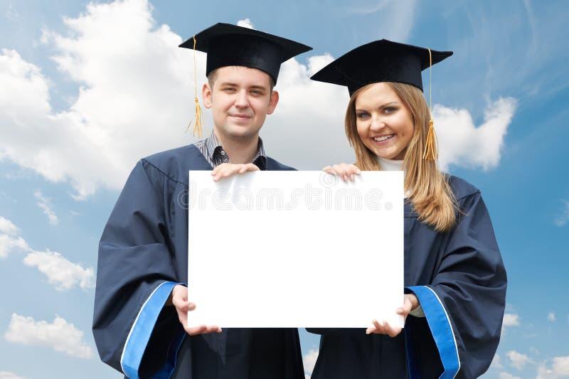 Étudiants de troisième cycle avec le panneau blanc photo stock