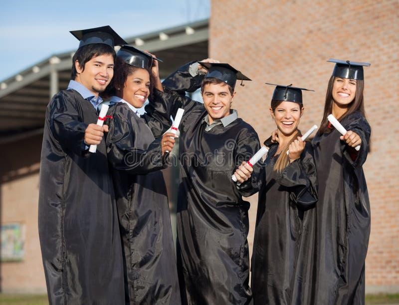 Étudiants de troisième cycle tenant des certificats dessus photo stock