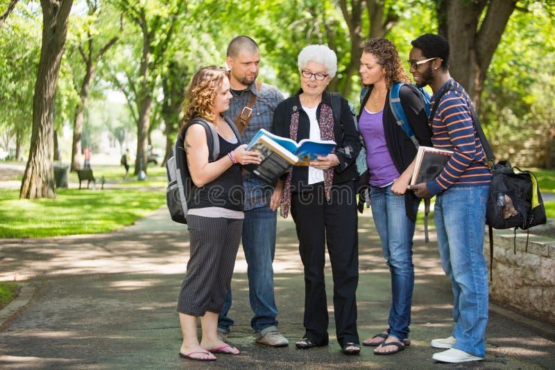 Étudiants discutant des notes sur la route de campus photo stock