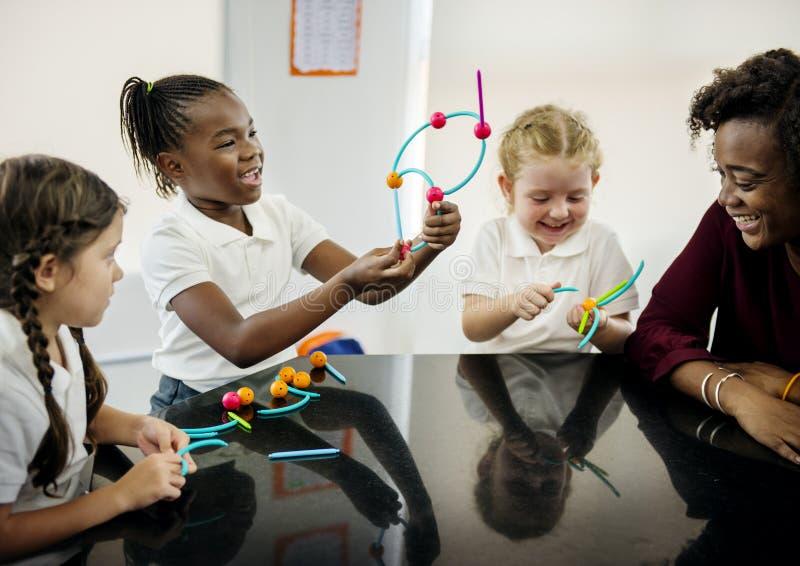 Étudiants divers de jardin d'enfants tenant apprendre des structures de t photographie stock