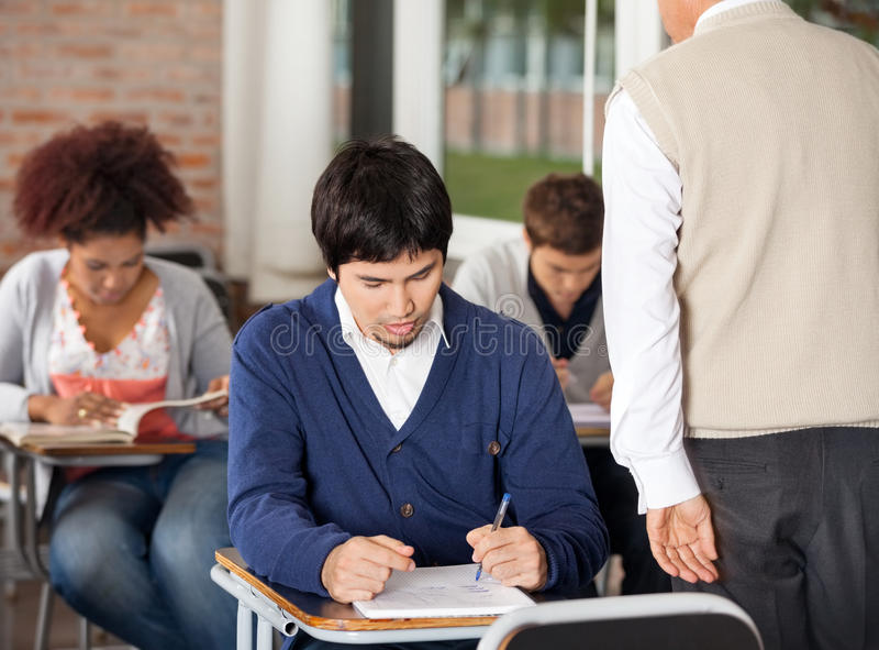 Étudiants donnant l'examen tandis que professeur Supervising photo libre de droits