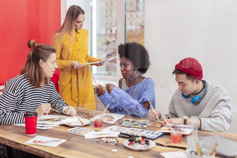 Étudiants en art doués élégants se sentant inspirés et occupés photographie stock libre de droits