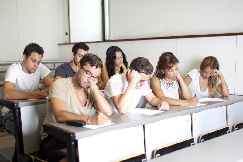 Étudiants ennuyés étudiant dans la chambre de classe images libres de droits