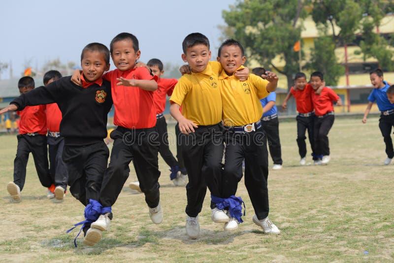 Étudiants enthousiastes d'école concurrençant dans la course trois à jambes image stock