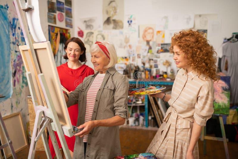 Étudiants et professeur d'art souriant tout en peignant et parlant image libre de droits