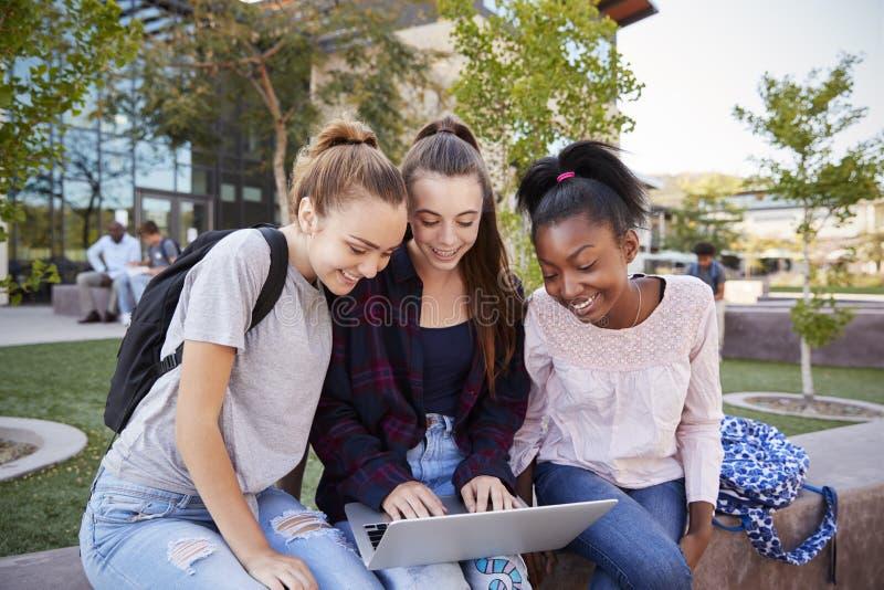 Étudiants féminins de lycée à l'aide des dispositifs de Digital dehors pendant le renfoncement photos libres de droits