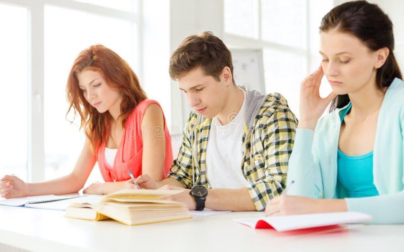 Étudiants fatigués avec des manuels et des livres à l'école photos libres de droits