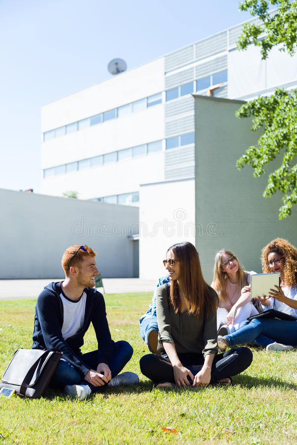 Étudiants heureux s'asseyant dehors sur le campus à l'université images stock