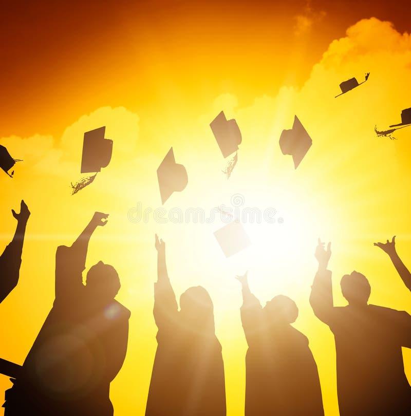 étudiants jetant des chapeaux d'obtention du diplôme dans le ciel images libres de droits