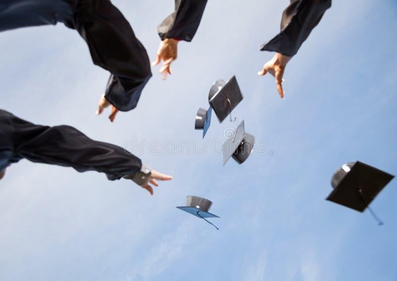 Étudiants jetant des panneaux de mortier en air contre le ciel image libre de droits