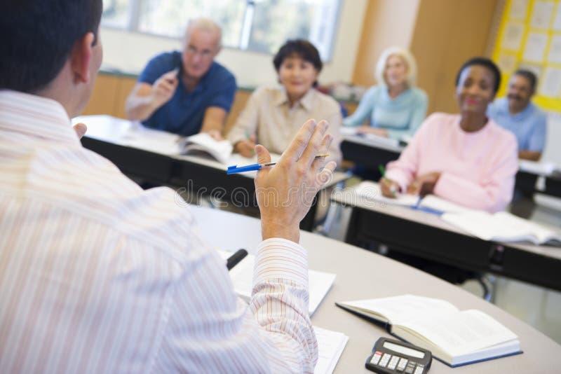 Étudiants mûrs et leur professeur dans une salle de classe photo libre de droits