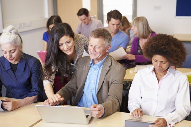 Étudiants mûrs dans la classe d'éducation plus permanente avec le professeur image stock