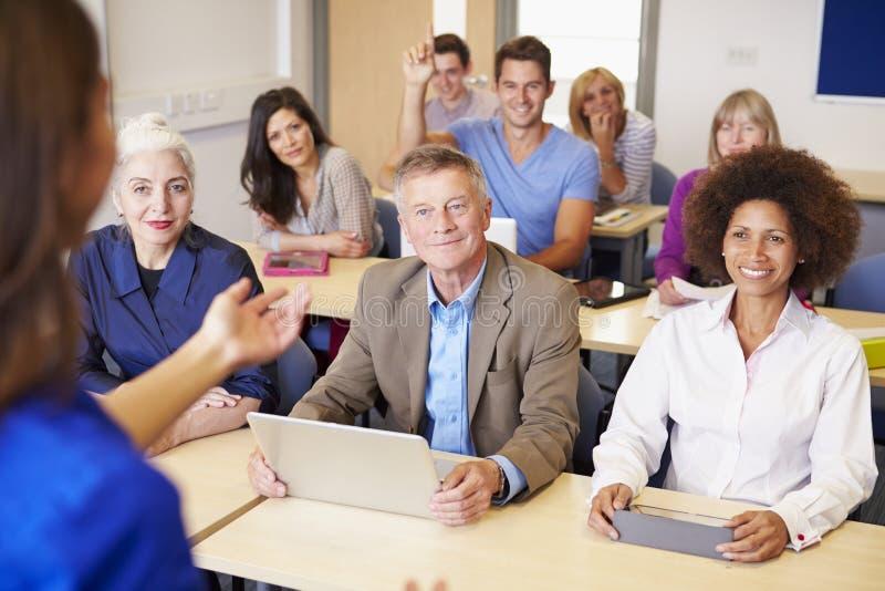 Étudiants mûrs dans la classe d'éducation plus permanente avec le professeur images libres de droits