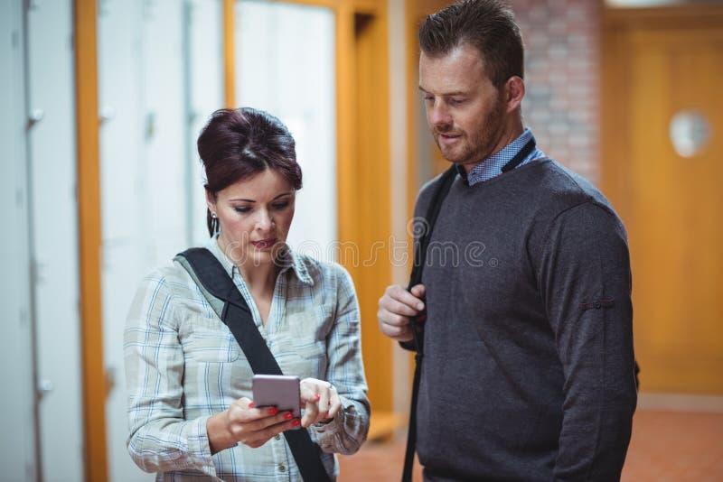 Étudiants mûrs discutant au-dessus du téléphone portable image stock