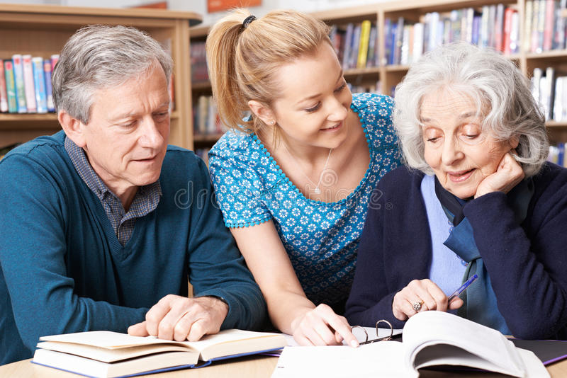 Étudiants mûrs travaillant avec le professeur In Library photos stock
