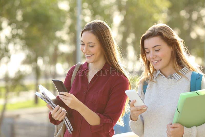 Étudiants marchant avec les téléphones intelligents image libre de droits