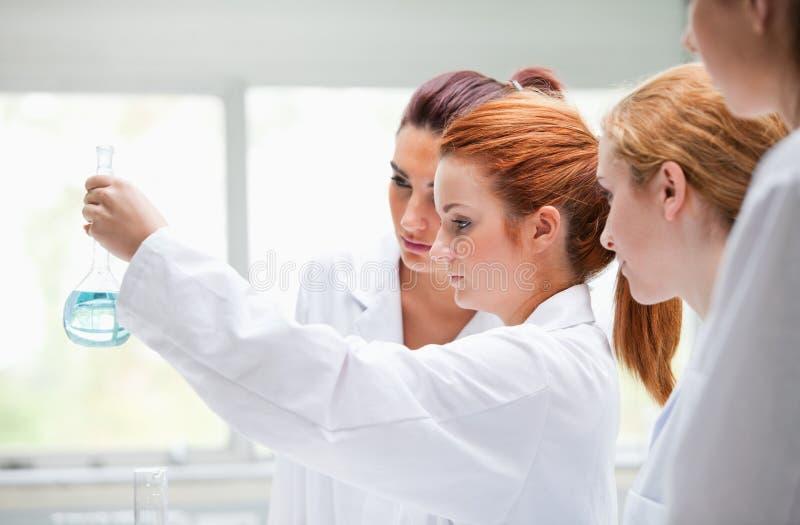 Étudiants mignons de chimie retenant un flacon photos libres de droits