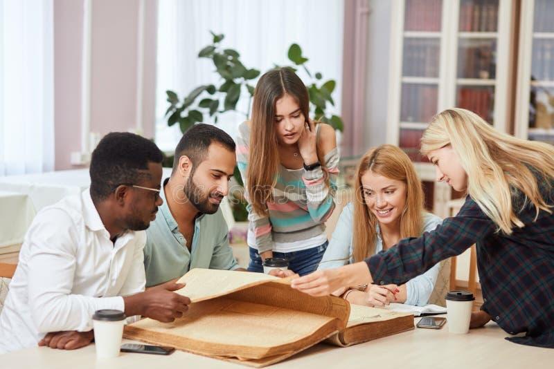 Étudiants multiraciaux divers passant le temps libre dans la bibliothèque avec le grand vieux livre photos stock